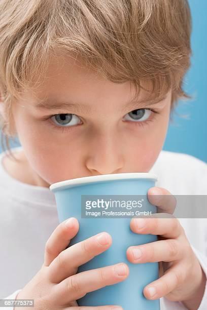 Little boy drinking milk out of blue beaker