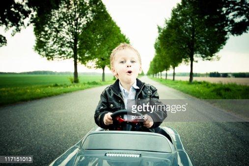 Little Boy Driving a Toy Car