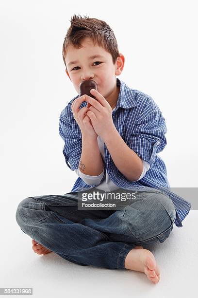 A little boy eating a chocolate marshmallow