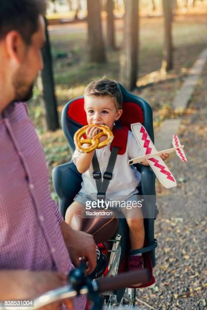 Kleiner Junge eine Brezel zu essen, in einem Kindersitz auf dem Fahrrad.