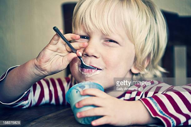 Little boy eating a yoghurt