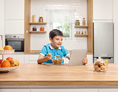 Little boy eating cereals for breakfast at a wooden counter and watching a tablet in a kitchen