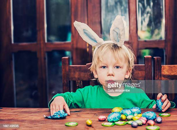 Little boy eating chocolate Easter eggs