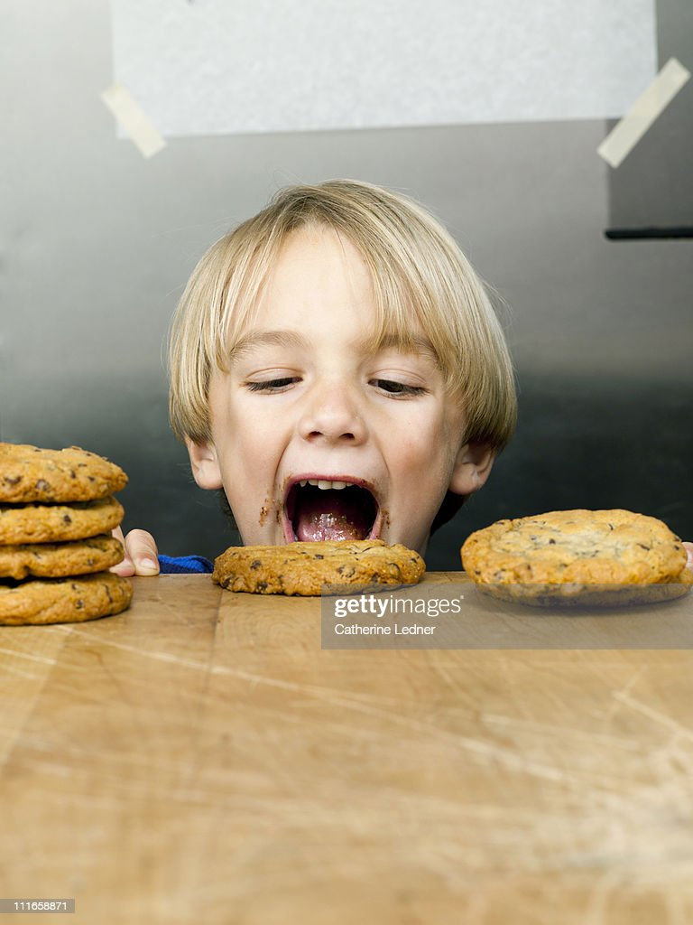 Little boy eating cookies off of a table