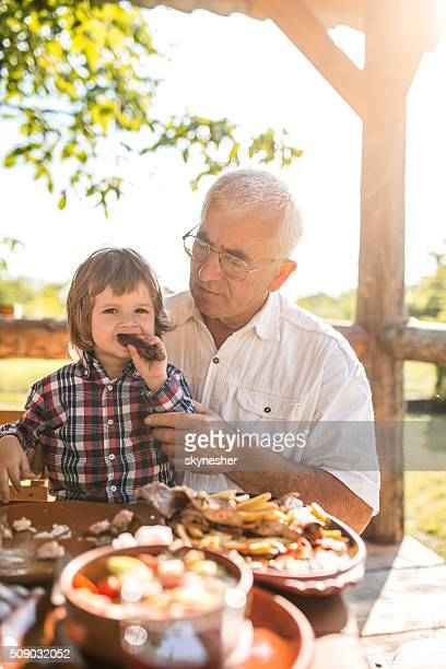 Little boy eating in a restaurant with his grandfather.