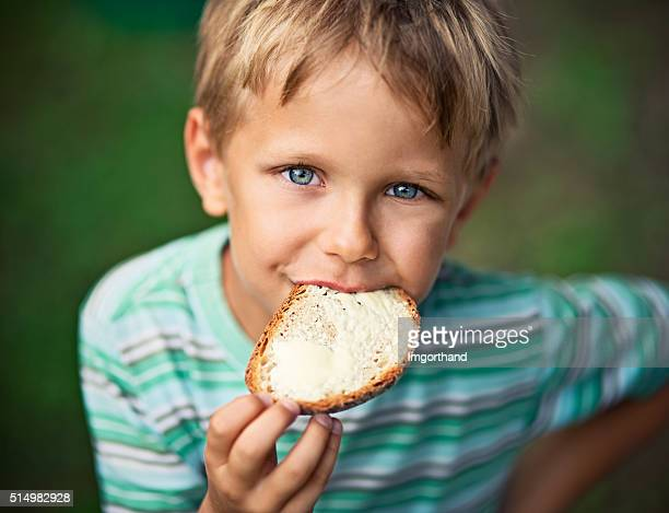 Little boy eating loaf of bread with butter