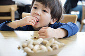 Little boy eating peanuts at a table in a restaurant
