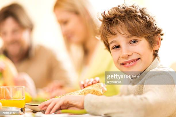 Little boy eating sandwich.