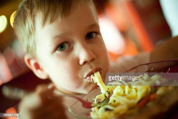 Little boy eating spaghetti with his mouth full
