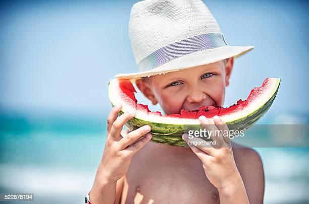 Petit garçon manger pastèque sur la plage