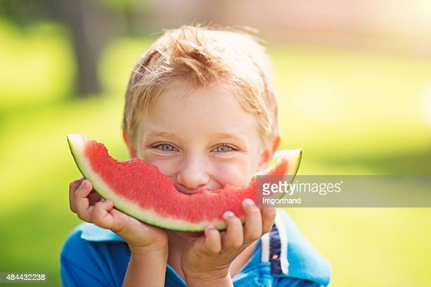 Little boy eating watermelon outdoors