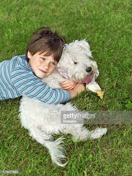 Little boy embracing his dog