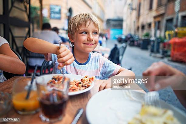 Little boy enjoying lunch in Rome street restaurant