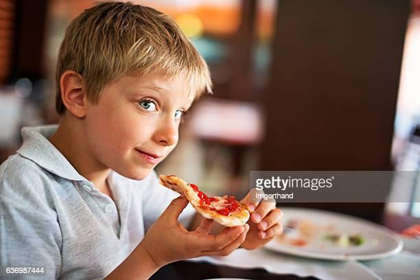 Little boy enjoying pizza lunch
