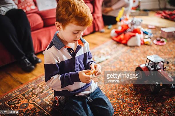 Little Boy Enjoys a Tangerine on Christmas Day