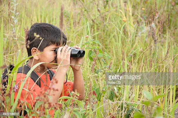 Little boy explores outdoors,nature using binoculars.  Tall grass.  Summer.