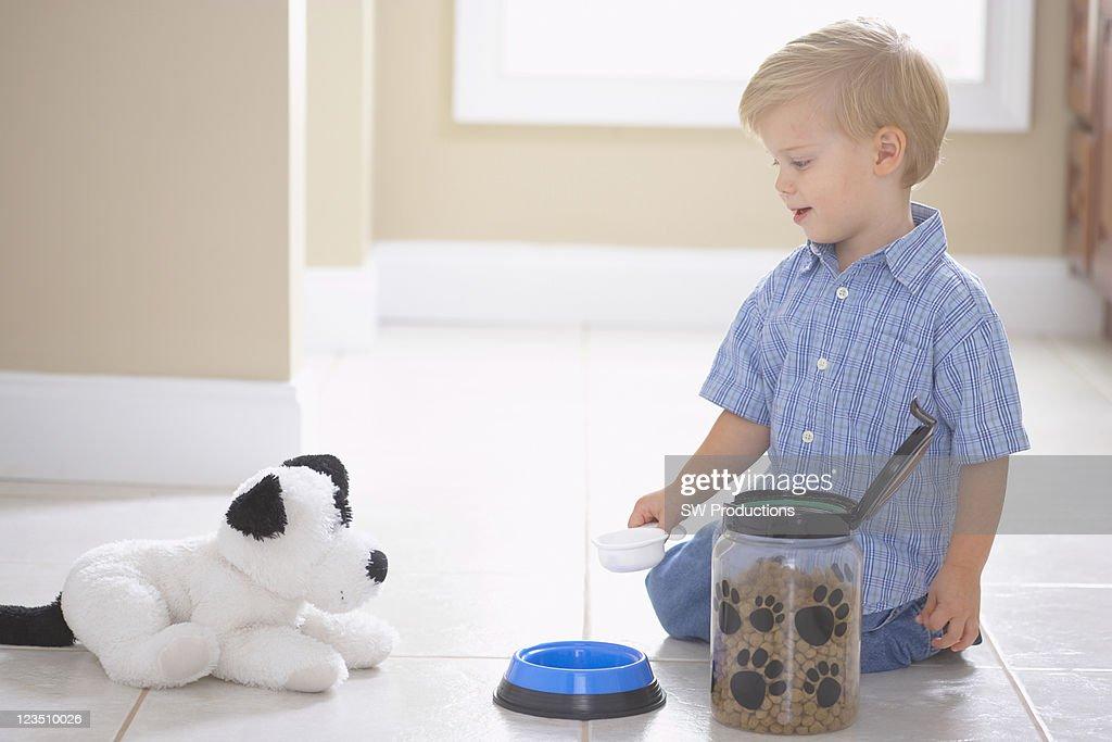 Little boy feeding dog food to stuffed animal on bathroom floor : Stock Photo