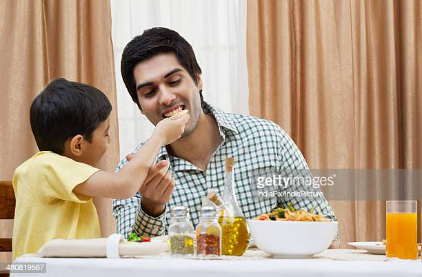 Little boy feeding piece of pizza to father at restaurant table