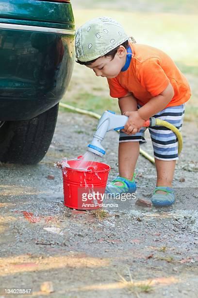 Little boy filling water in bucket