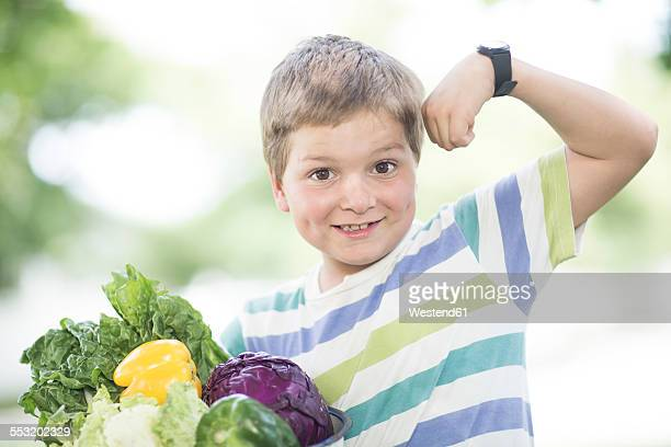 Little boy flexing muscles with bowl of mixed vegetables