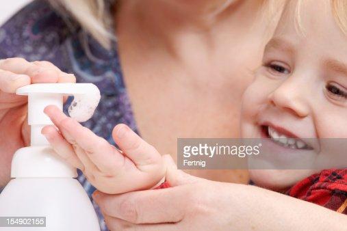 Little boy getting help using a hand sanitizer