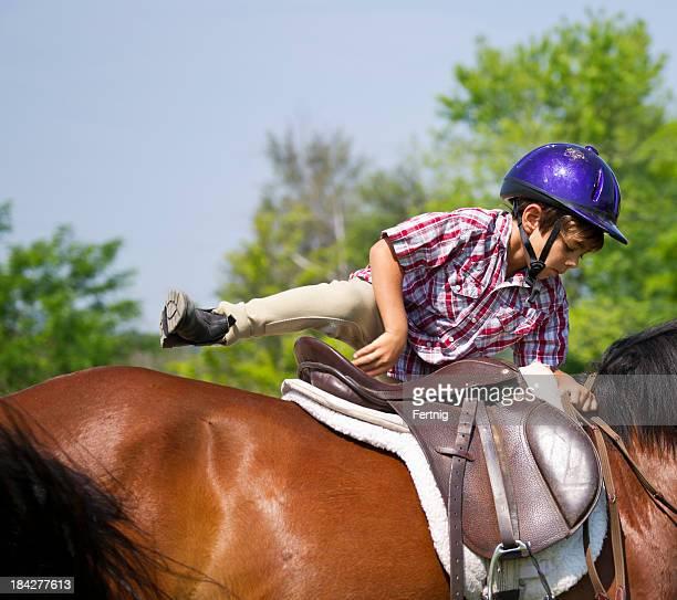 Little boy getting on a pony