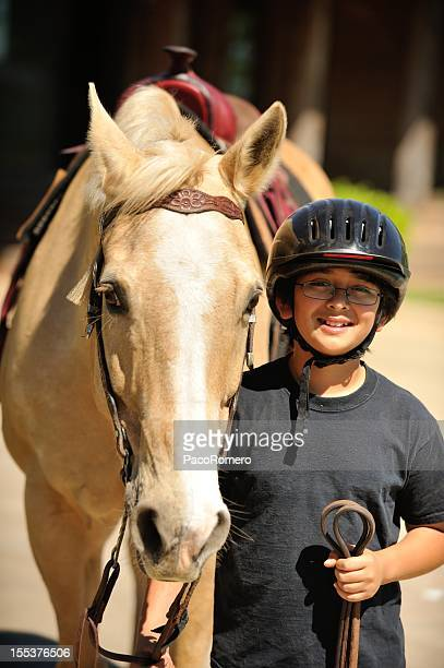Little boy getting ready to ride his horse.