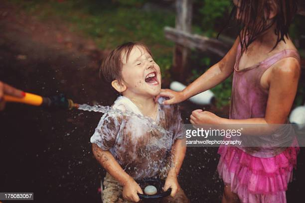 little boy getting sprayed with water