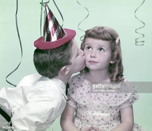 A little boy gives a little girl a peck on the cheek during a birthday party ca1950s United States