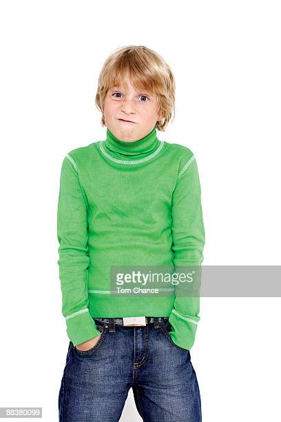 Boy (10-11) standing with hands in pockets, grimacing, portrait