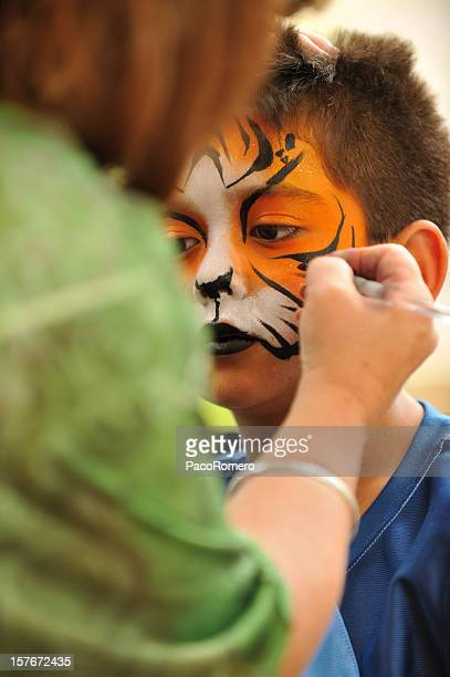 Little  boy having a tiger mask painted on his hace