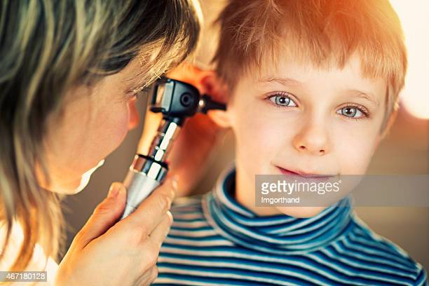 Little boy having ear examination at home.