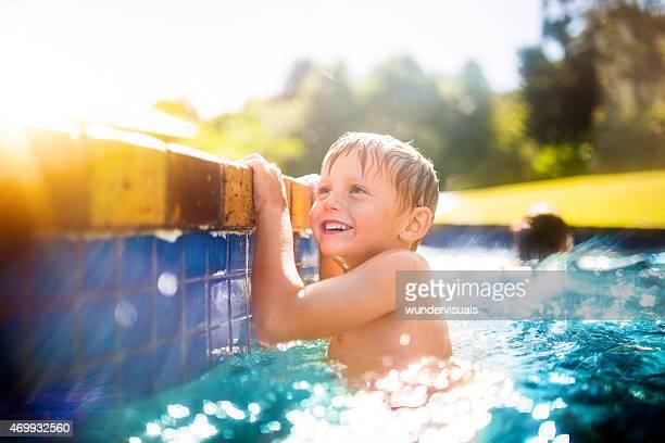 Poco niño divirtiéndos'en la piscina de verano