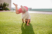 Playful boy doing handstand and having fun on the grass in nature.
