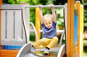 Little boy having fun on outdoor playground/on slide. Summer active sport leisure for kids