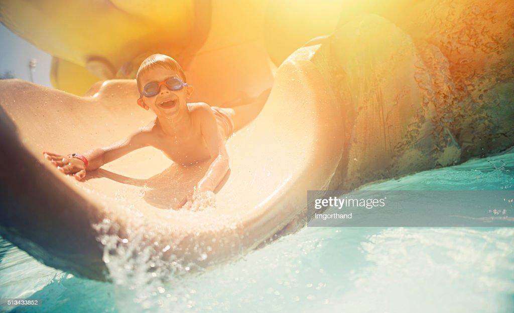 Little boy having fun sliding in water park : Stock Photo