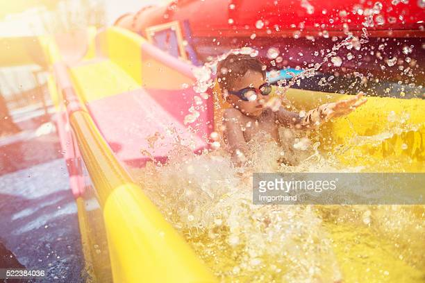 Little boy having fun sliding in water park