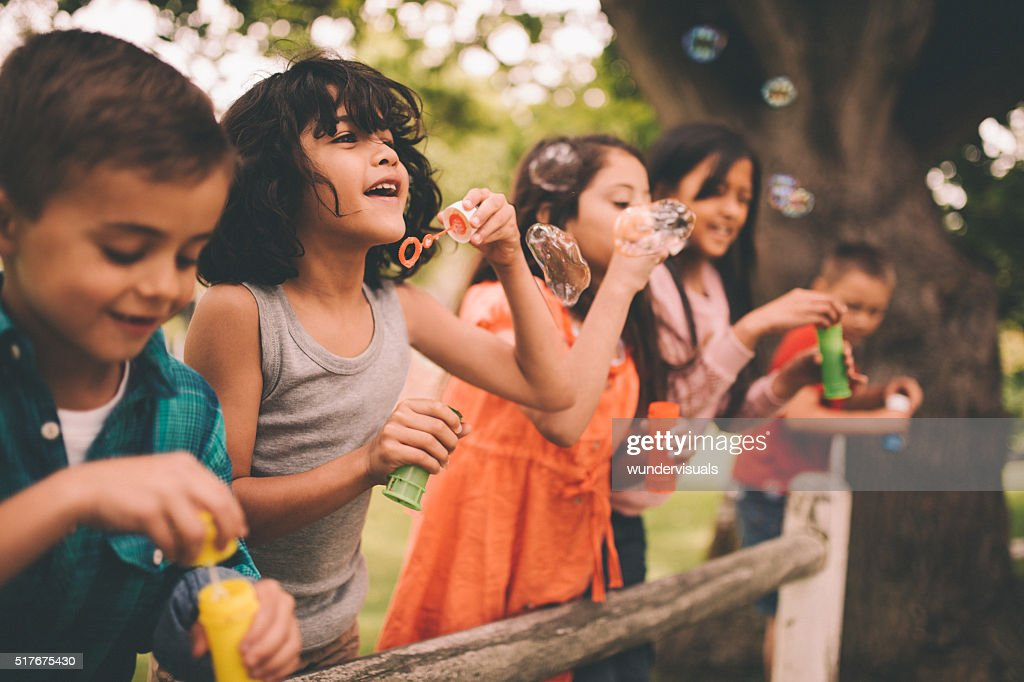 Little boy having fun with friends in park blowing bubbles : Stock Photo