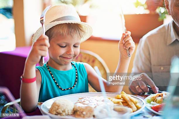 Little boy having meal at restaurant