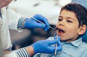 Little boy having regular dental check-up. Toned image