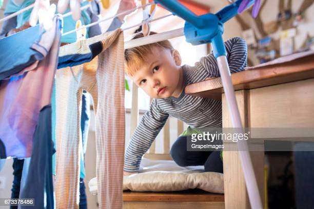 Little boy helping his unrecognizable mother to hang clothes on the rack