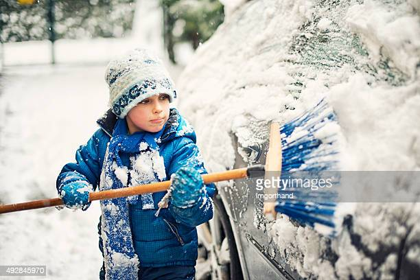 Little boy helping to clean family car after winter attack