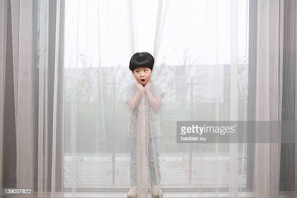 Little boy hiding behind curtain