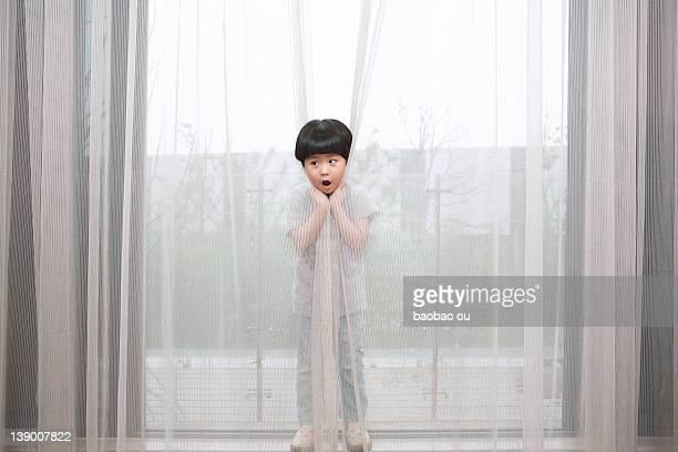 Little boy hiding behind curtain