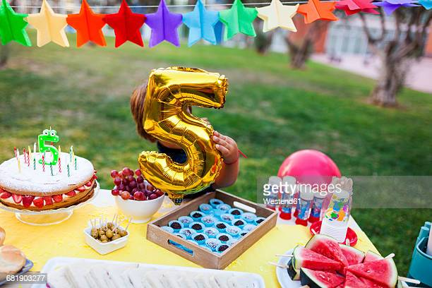 Little boy hiding behind golden balloon at laid birthday table