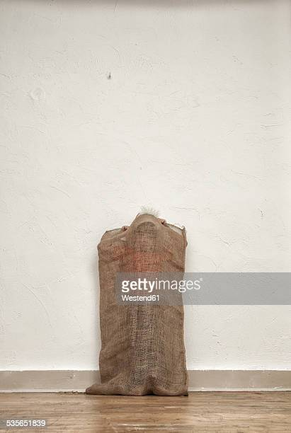 Little boy hiding in gunny bag