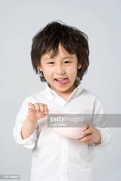 Little boy holding a bowl and spoon