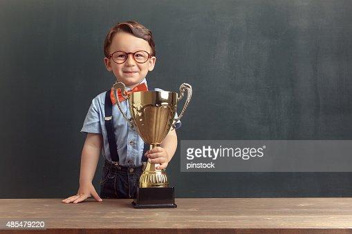 Little boy holding a golden trophy