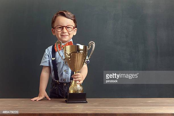 Little boy holding a golden trophy