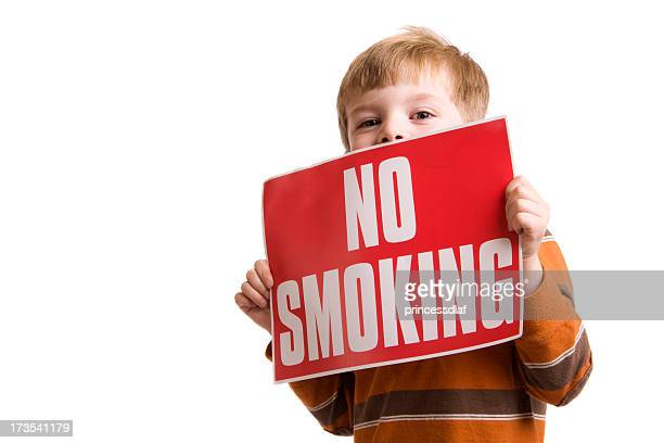 Little boy holding a red sign that says NO SMOKING